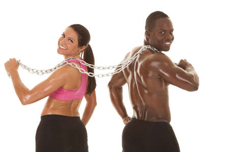 An interacial couple working out with a chain smiling.
