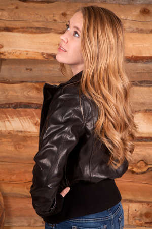 a woman in her leather jacket looking up