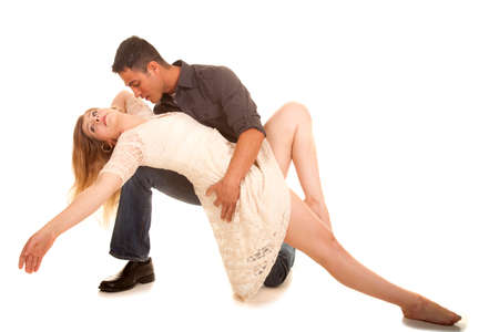 a couple doing a dance pose, he is on his knee, he is looking at her.