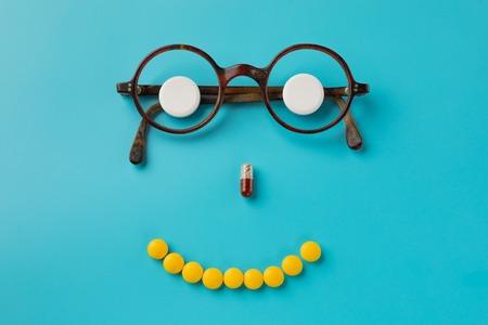 pills. glasses, blue background. Black Eye Glasses with white pills on blue background.