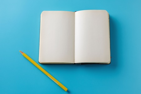 Photo for Mockup Blank page with yellow pencil. Top view with copy space for input the text. Flat lay, colored blue background. - Royalty Free Image