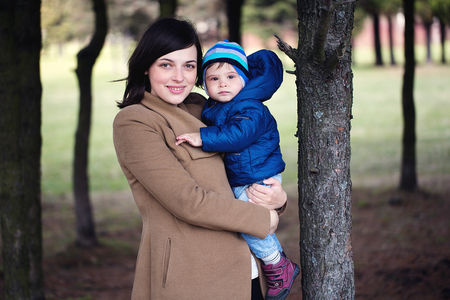 Foto de happy mother holding her little son in her arms in the park. girl and little boy in the forest. - Imagen libre de derechos