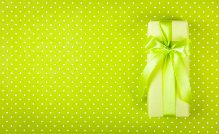 Gift box on light green background. Box with surprise on polka dot background. International Women\'s Day. Copy space. Top view
