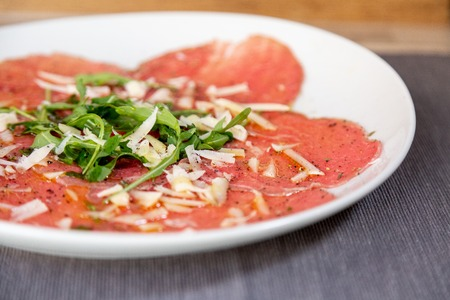 Photo for Close up of carpaccio meat with parmesan cheese and arugula in a white plate on a wooden table. With olive oil. - Royalty Free Image