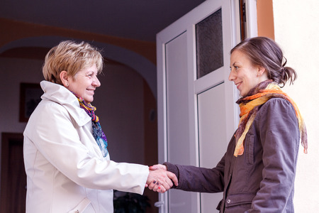 Photo pour Senior women greeting young girl in the doorway - image libre de droit