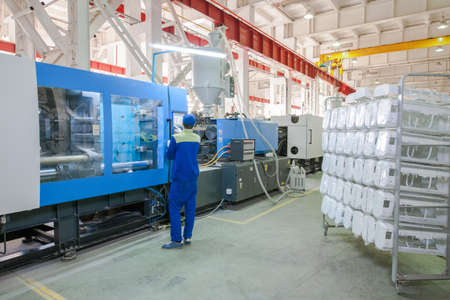 Photo pour Industrial injection molding press machine for the manufacture of conditioner parts using polymers in the management of worker - image libre de droit