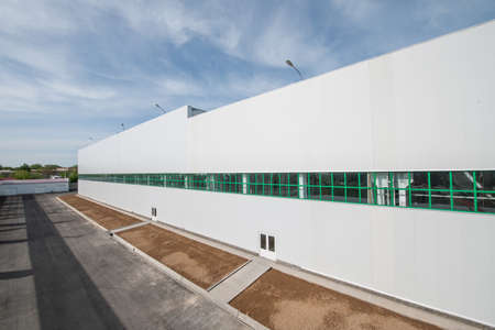 facade of an industrial building and warehouse in length with a place for flower beds and plants. panorama and perspective of an facade industrial building and warehouse
