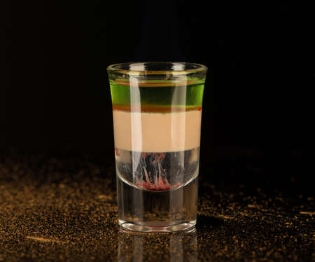 Photo pour mixed alcoholic liquor with cinnamon in a shot glass isolated on a black background - image libre de droit