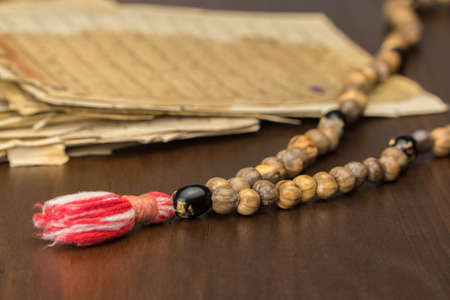Photo pour Muslim prayer beads with ancient pages from the Koran. Islamic and Muslim concepts. Ancient old sheets of paper from the Arabic book - image libre de droit