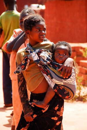 Young woman takes her child in arms on August 10, 2009 in North Lwanga National Park  Zambia