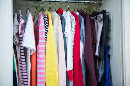 Photo pour Colorful clothes on hangers in well organized wardrobe at home. Choice of cotton clothes of different colors on hangers. Organizational space - management of environment - image libre de droit