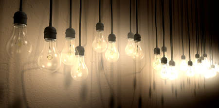 A front view row of displayed illuminated hanging lightbulbs casting various shadows on a br