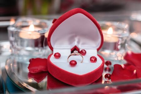 Photo pour Wedding ring in rose petals against the background of candles. - image libre de droit