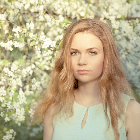 Beautiful girl with blond hair in the spring blooming garden