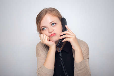 Photo pour Young caucasian woman is talking on the landline phone, bored, tired or annoyed - image libre de droit