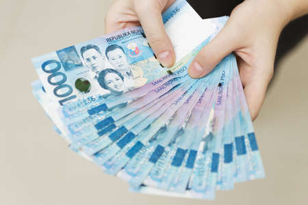 Photo pour Hands holding salary or payment bundle of cash of one thousand philippines peso as if being rich. Show off, pay bills or give bribe. - image libre de droit