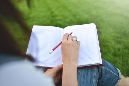 Photo pour close up young women writing on notebook in park. education and knowledge concept - image libre de droit