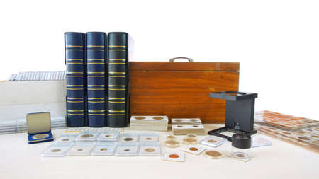 Coins of different countries of the world on white table with folders and supplies background - Numismatic scene