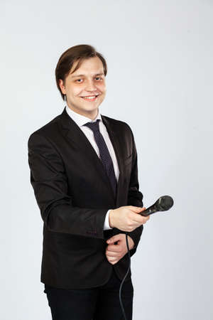The interviewer. Young elegant man holding microphone