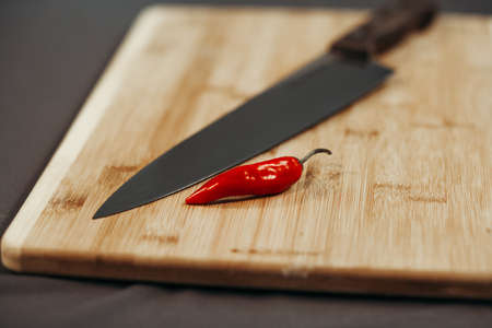 Red Chilli on the old wooden chopping board and shiny knife next to them