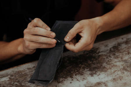Working process of the leather wallet in the workshop. Man holding leather craft and working. Close up of leather craftsman working with natural leather. Handmade concept.
