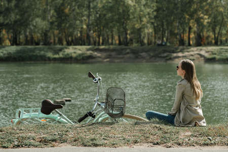 Photo for Young woman with vintage bicycle on the lawn near the lake - Royalty Free Image