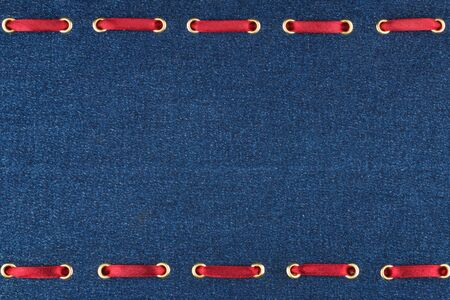 Fashionable background red satin ribbon inserted in denim, with space for your creativity