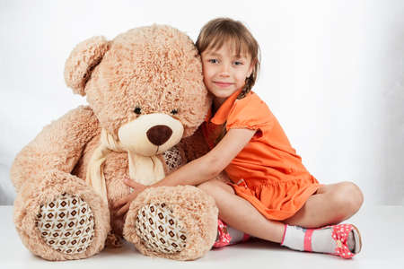 Photo pour Cute little girl playing with her friend big fur bear. Baby girl hugging her teddy bear - image libre de droit