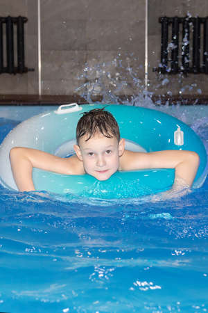 Photo pour Beautiful happy boy swims in the pool with a circle - image libre de droit