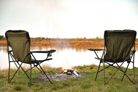 Photo pour A pair of tourist armchairs, a folding chair, a bonfire on the river bank in the evening at sunset, twilight in autumn at sunset, relaxation and rest, the beginning of autumn, tourism and travel, a close-up of a copy space - image libre de droit