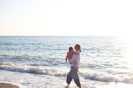 Photo pour mom and daughter are playing on the sandy beach. - image libre de droit