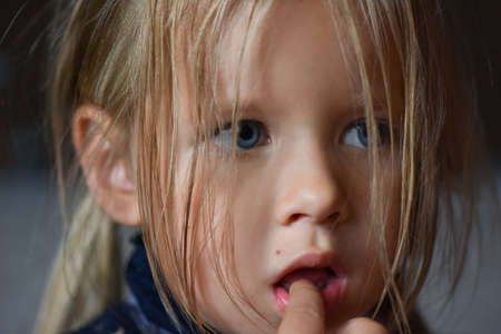 Photo pour Portrait of sad romantic little girl with big blue eyes and a finger in her mouth from Eastern Europe, close-up, dark background - image libre de droit