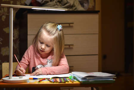 Foto de Child preschooler learns to draw and write in notebooks at home in the evening under the light from desk lamp - Imagen libre de derechos