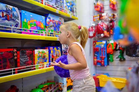 Photo pour Girl looks in the window of children toy shop. - image libre de droit