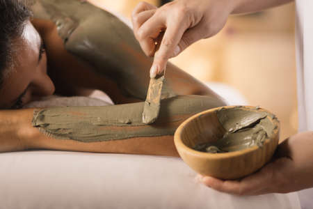Photo for Closeup of applying mud mask with hands of professional therapist. - Royalty Free Image