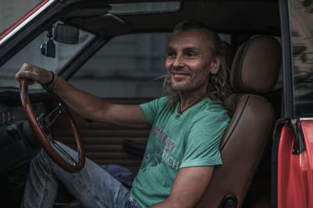 Photo for Portrait of mature handsome man sitting in red old style car, holding steering wheel and smiling. Long gray hair. 1970s style red car. High quality - Royalty Free Image