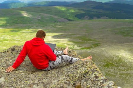 businessman in a red sweatshirt is sitting on a rock on a mountainside barefoot in seclusion with a noteboock in hand against a background of a green valley of hills.the manager works in the open air