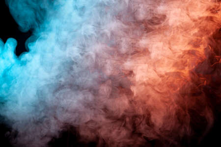 Foto de Translucent, thick smoke, illuminated by light against a dark background, divided into three colors: blue, green, pink and purple, burns out, evaporating from a steam of vape for print on t-shirt - Imagen libre de derechos