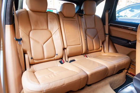Photo pour Clean after washing the rear passenger seats of matte brown or beige genuine leather inside the interior of an expensive luxury suv, preparation before selling the car. - image libre de droit