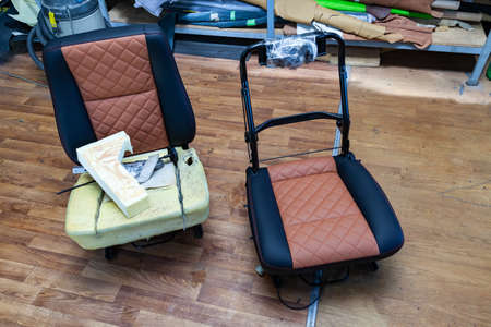 Photo pour Two front seats with combined leather trim in double colors of black and brown with shape of rhombus and the visible part of the frame located on the floor in the workshop for repair and tuning of car - image libre de droit
