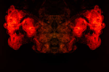 Photo pour Smoke of different orange and red colors in the form of horror in the shape of the head, face and eye with wings on a black isolated background. Soul and ghost in mystical symbol - image libre de droit