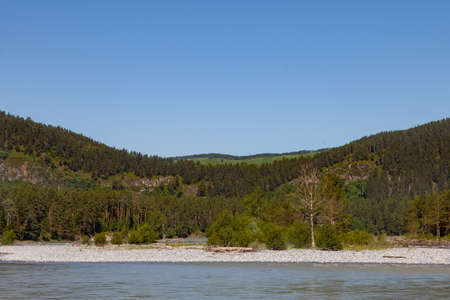 summer landscape on the river with stones and two mountains covered with green coniferous trees. travel and outdoor recreation.
