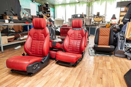 Photo pour Four sport seats with red leather trim, located on the floor in the workshop for repair and tuning of cars and vehicles - image libre de droit