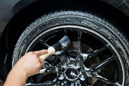 Photo pour A male worker washes a black car with a special brush for cast wheels and scrubs the surface to shine in a vehicle detailing workshop. Auto service industry. - image libre de droit