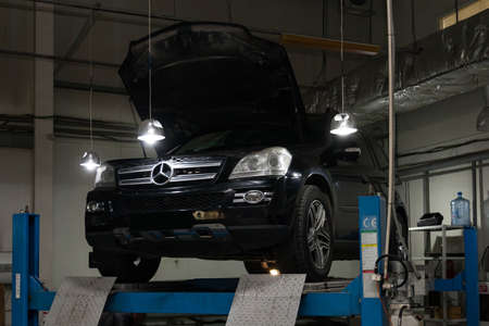 Novosibirsk, Russia - 08.01.2018: Used black car Mercedes Benz GL with an open hood raised on a four-post lift for repairing the chassis and engine in a vehicle repair shop. Auto service industry.