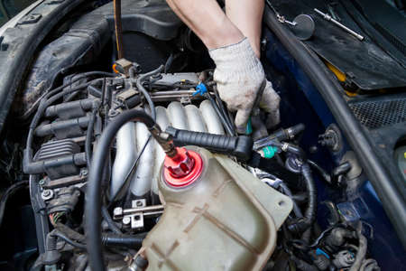 Photo pour A car repairman unscrews parts with a wrench with a green handle in the engine compartment suh as spark plugs and ignition coils in a vehicle repair workshop. Auto service industry. - image libre de droit