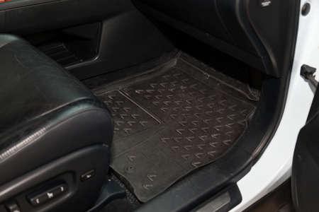 Foto de Dirty car floor mats of black rubber under passenger seat in the workshop for the detailing vehicle before dry cleaning. Auto service industry. Interior of sedan. - Imagen libre de derechos