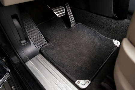 Foto de Dirty car floor mats of black carpet with gas pedals and brakes in the workshop for the detailing vehicle before dry cleaning - Imagen libre de derechos