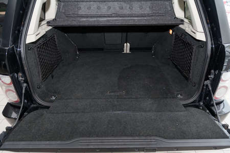 Foto de Open empty trunk of a car suv close-up before washing and vacuuming with a carpet floor mat of special black material ready for loading luggage. Auto service industry. - Imagen libre de derechos