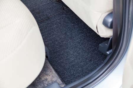 Foto de Clean car floor mats of black carpet under rear passenger seat in the workshop for the detailing vehicle before dry cleaning. Auto service industry. Interior of sedan. - Imagen libre de derechos